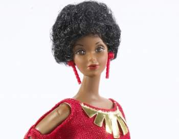Vintage Black Barbie doll wearing a red dress with exposed shoulders, gold embellishments, and matching red earrings.