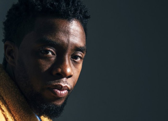 Photo of Chadwick Boseman, facing camera, to the left of the frame with right side of face shadowed. Golden brown coat collar visible.