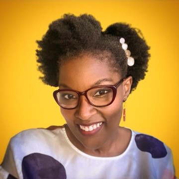 Aisha Adkins, a Black woman in her thirties with short, natural hair and glasses, smiles in front of a marigold yellow background.